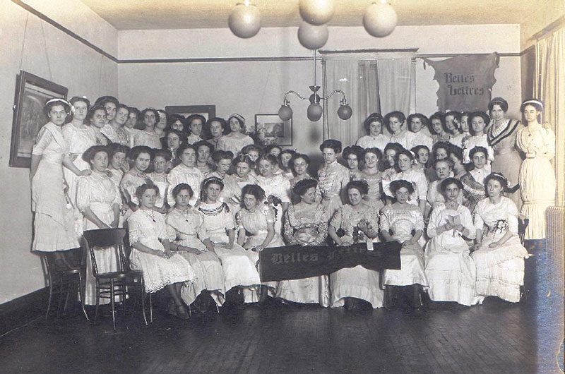 A photo of a large group of female students posing for a photo with a Belles Lettres banner on the wall behind them.  Several students in the front row are also holding a Belles Lettres banner.
