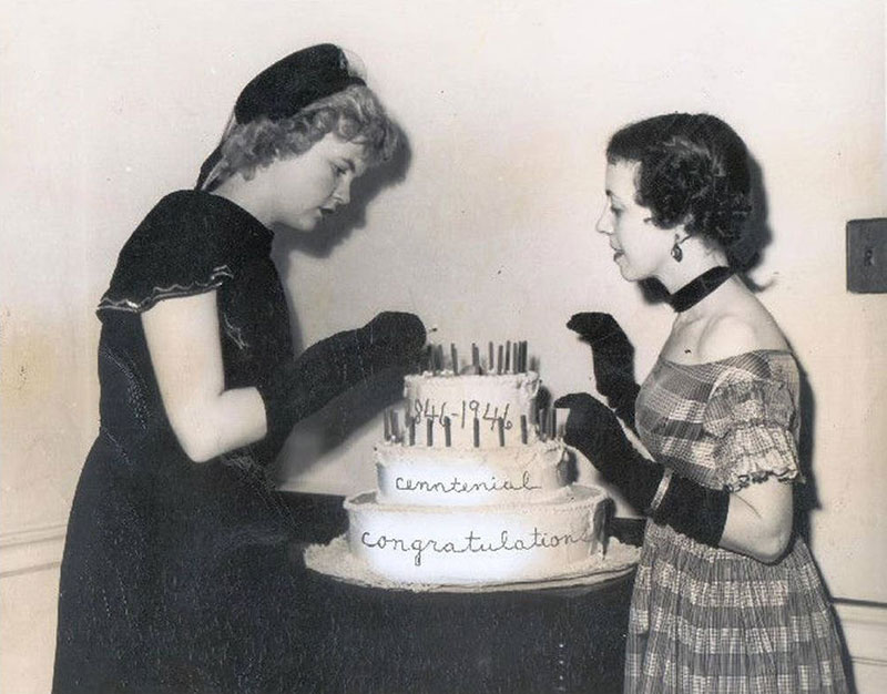 "A photo of two female students wearing clothes appropriate for the 1840s lighting candles on a cake that reads ""1846-1946 Centennial Congratulations""."