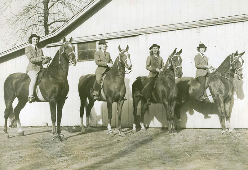 A photo of four female students on horseback in front of a stable.