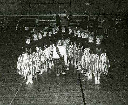 A photo of a male student dressed as a highlander with female cheerleaders joining him on either side.