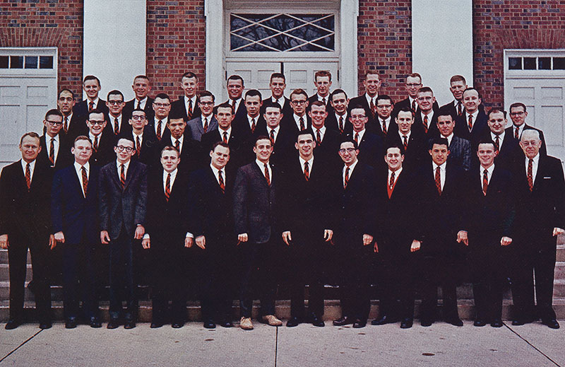 A photo of a group of all-male students standing on the steps of Annie Merner Chapel.